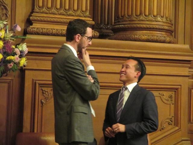 Scott Wiener and David Chiu confer before the vote