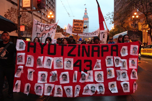 Pictures of the disappeared adorn a protest banner