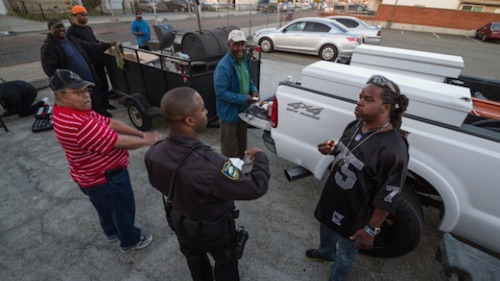 Officer Brandon Ruffin chats with a group of locals barbecuing in the Veteran's Memorial Hall parking lot. (Photo by Martin Totland, courtesy of Richmond Confidential)