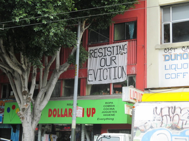 A sign in the window shows that the tenants are serious about fighting  an attempt to displace them