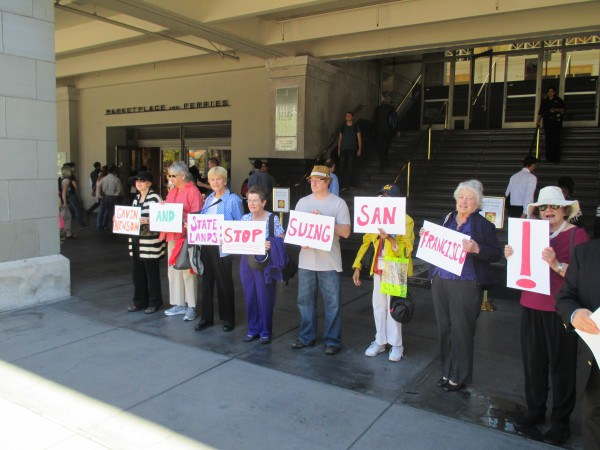 Protesters in front of a State Lands Commission meeting call for an end to the lawsuit against the city
