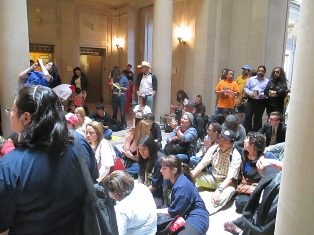 Protesters sit in front of Mayor Lee's office to demand a halt to luxury housing in the Mission