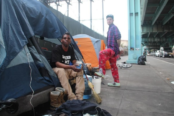 Ashante Jones sits in his tent while Jeremy Harvell looks on
