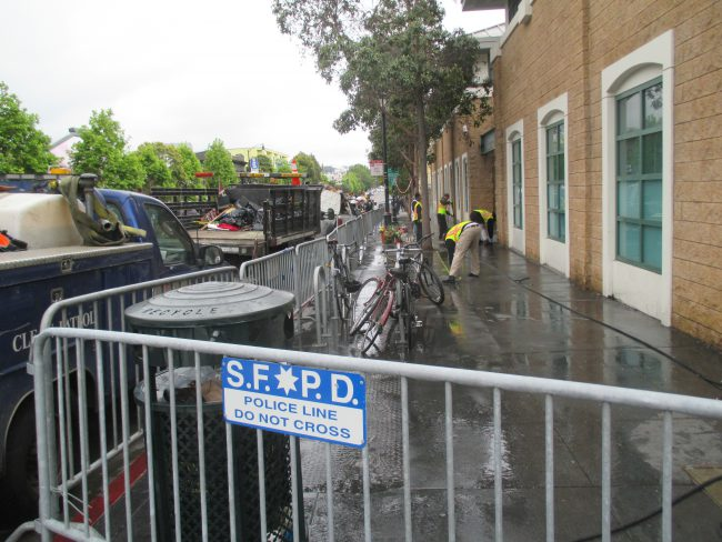 DPW hoses down closed sidewalk in front of Mission Station. Photo by Michael Redmond