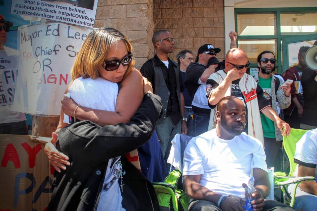 Gwen Woods, mother of Mario Woods, hugs Equipto after her emotional speech to the rally.