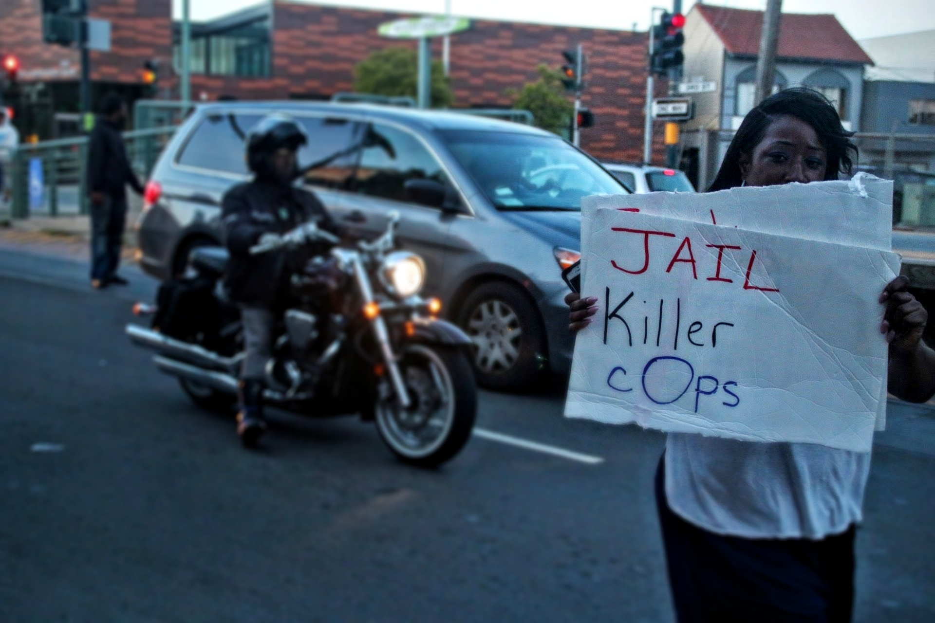 "Protestor holds a sign that says ""Jail killer cops."" Photo by Sana Saleem"