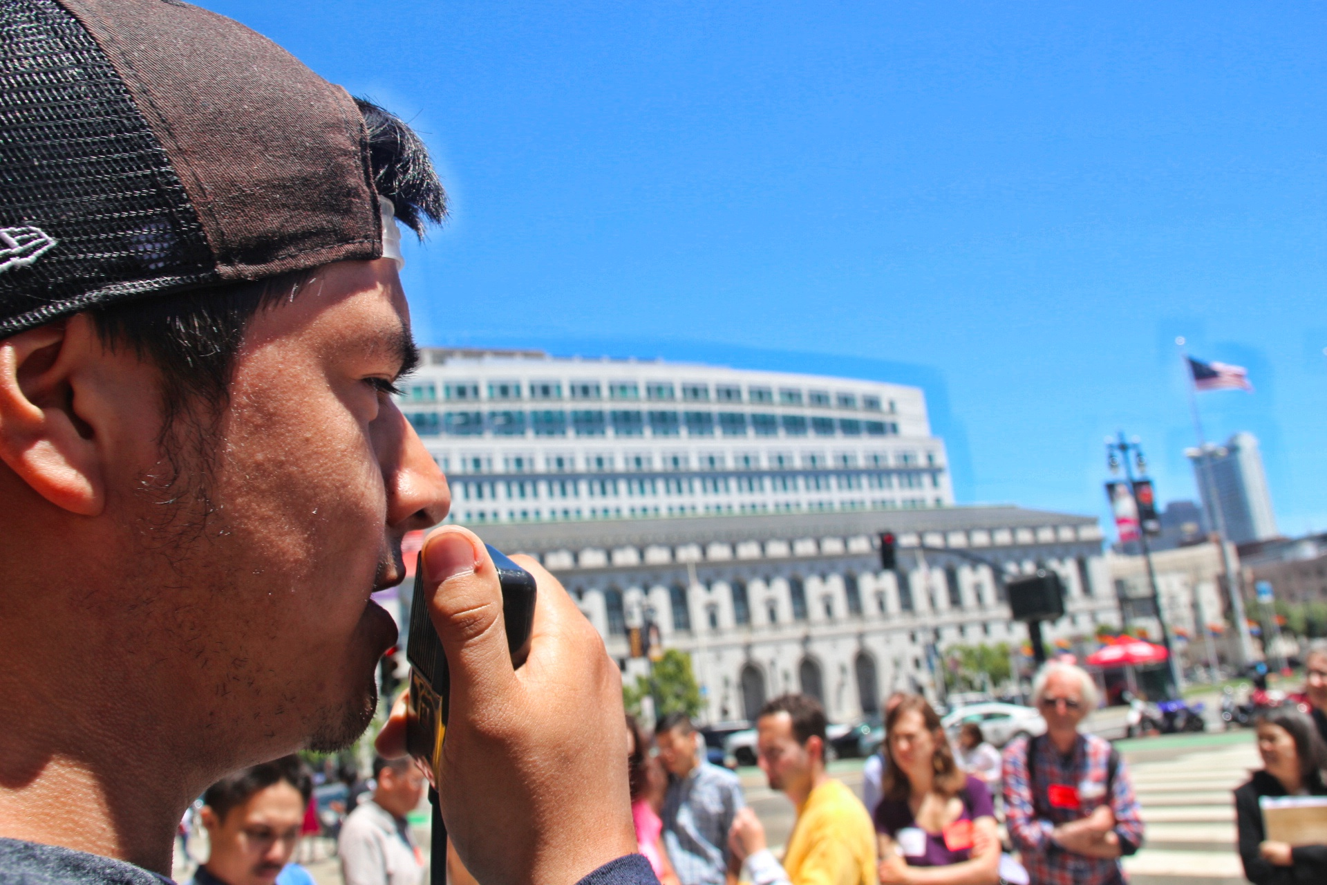 Daniel C, born and raised in the mission, speaks to a group outside City Hall. Photo by Sana Saleem.