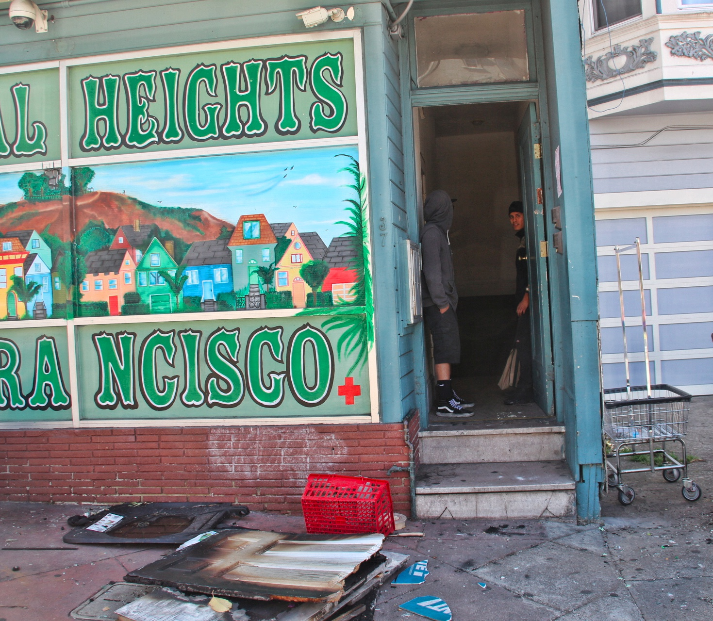 Residents stand at the doorstep of their building two days after the fire on 29th & Mission. Photo by Sana Saleem.