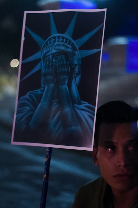 Mexican citizen hoists a sign showing the Statue of Liberty weeping at the Mexico City anti-Trump protest on Wednesday night. Photo by Sandra Blow
