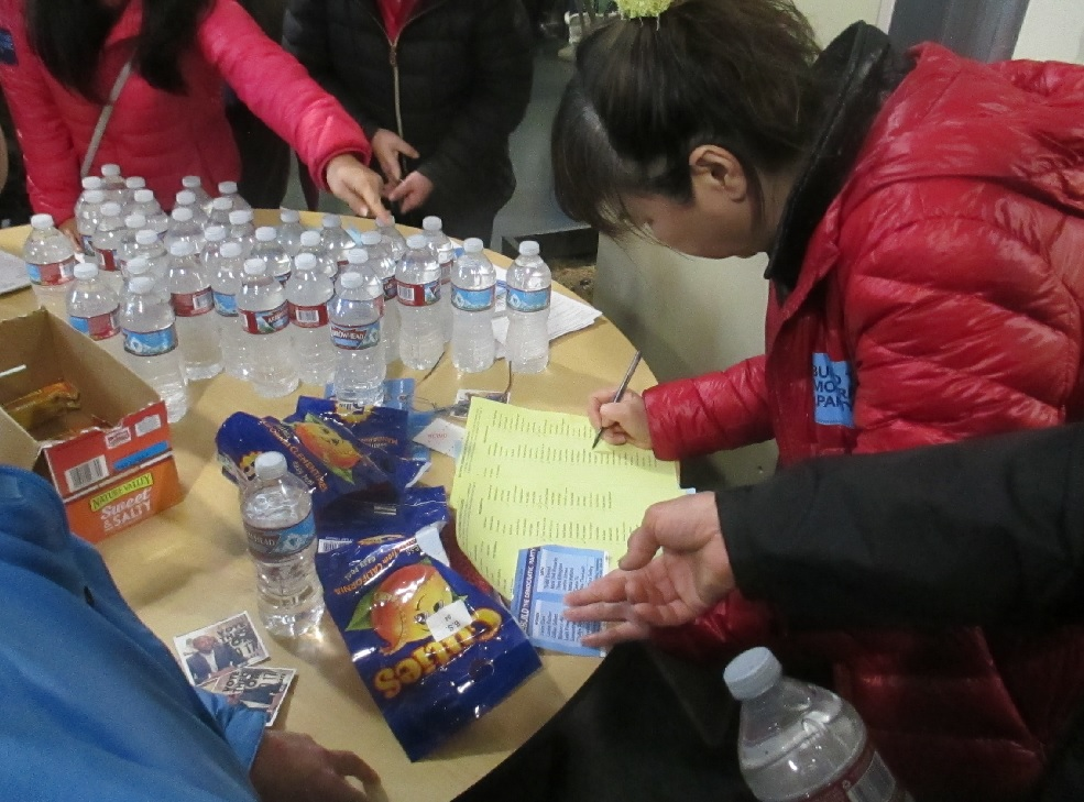 A supporter of the Chiu slate uses a card to fill out multiple ballots