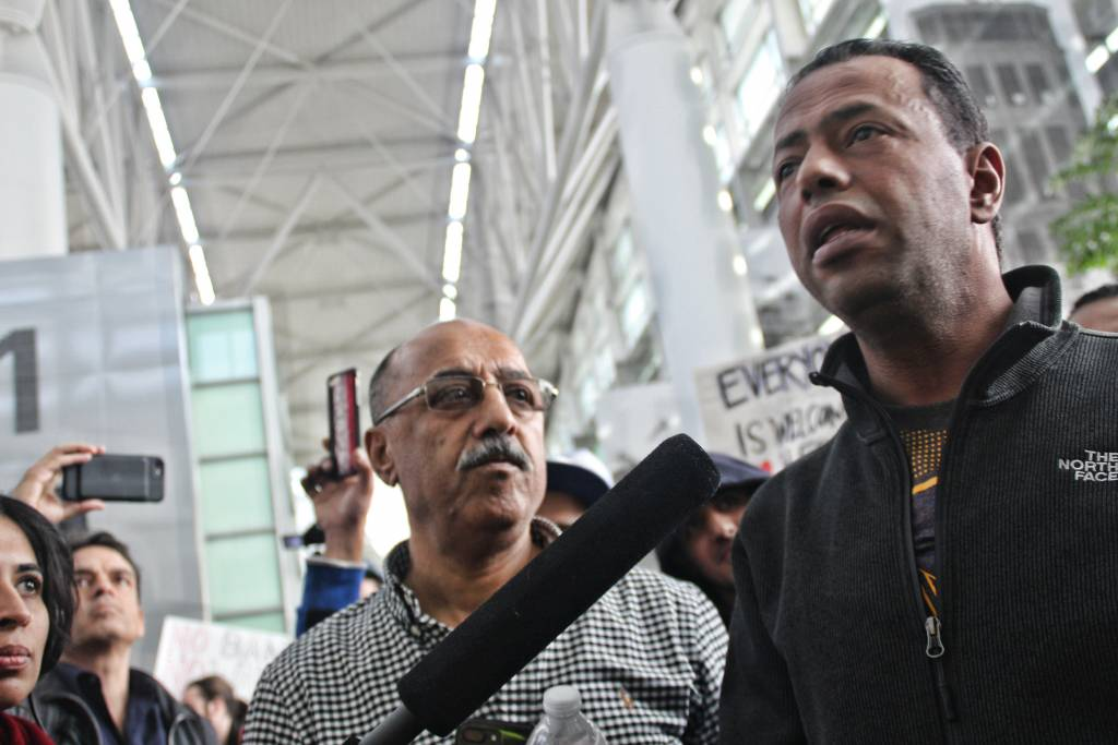 Mustafa Abuzeid, a Yemeni- America, stands alongside his father as he reunites with his family after being detained for 6 hours. Abuzeid has been a green card holder for the past 20 years and was returning home from Kaula Lumpur. Photo by Sana Saleem.
