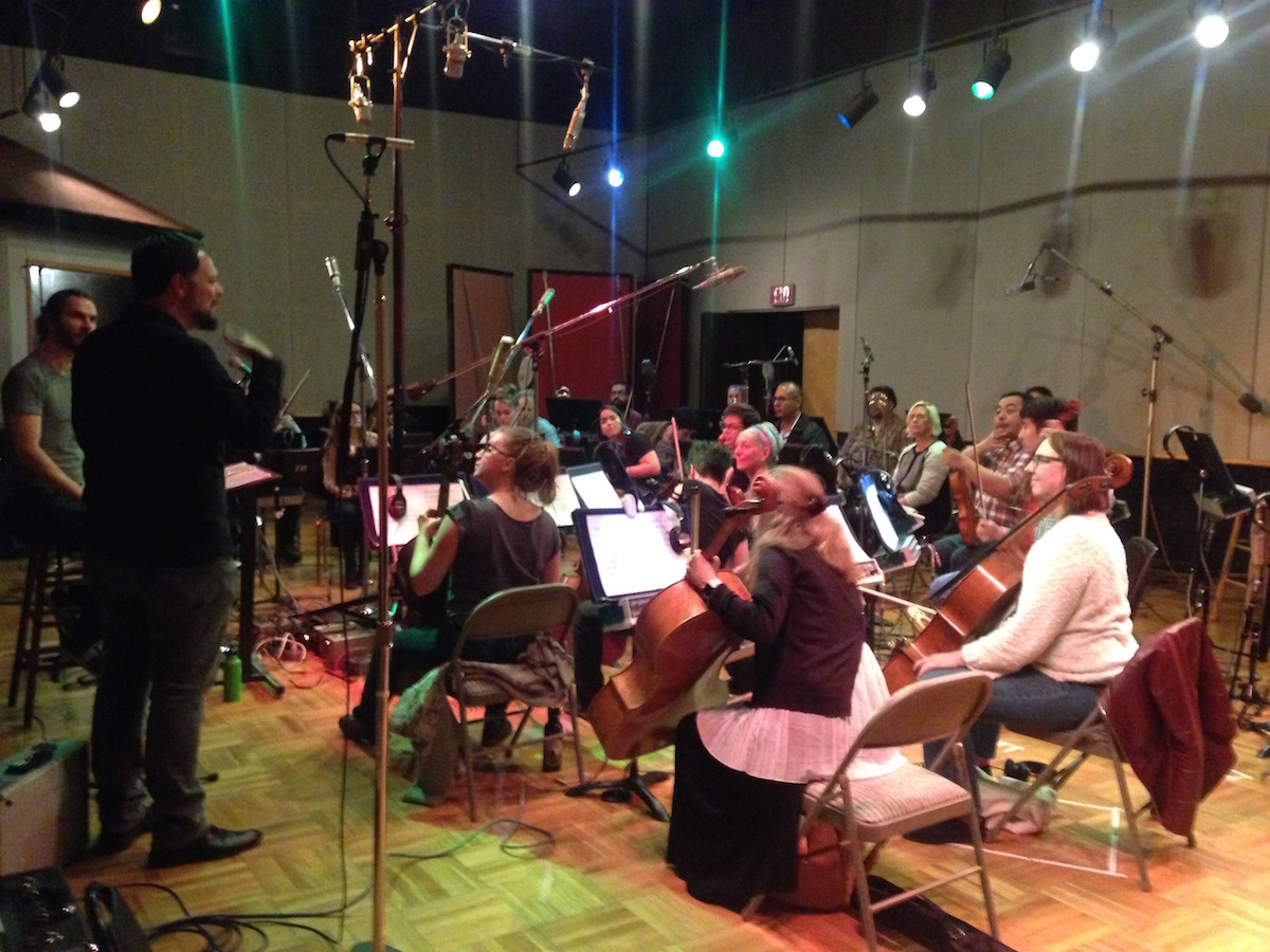 """Joe Bagale discussing his arrangement of """"A Day in the Life"""" with members of Awesome Orchestra. Photo by Joanna Ladd."""