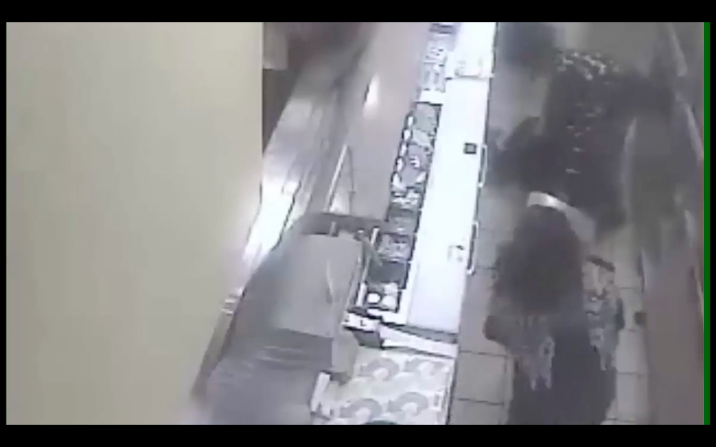Still from Subway surveillance video released by the SFPD.  A woman can be seen hitting Flusche with what appears to be a food tray as Flusche continues to hit the victim.
